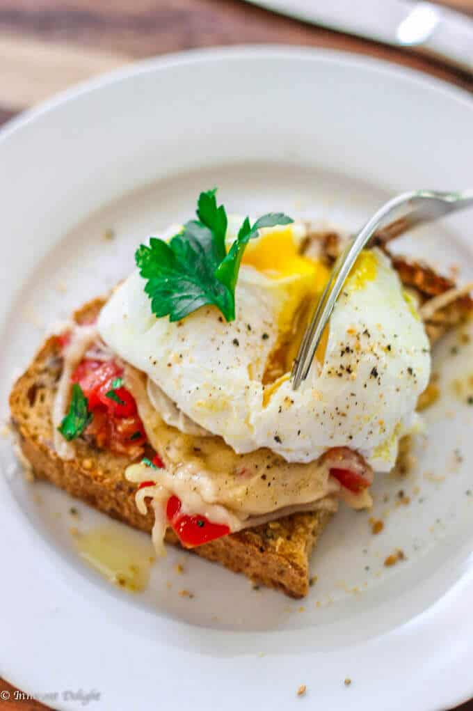 Poached Egg on Parmesan Tomato Toast is a delightful breakfast option. Runny egg yolk infuses with the tomatoes and herbs, and is beautifully balanced by a crusty parmesan topping - making for an irresistibly perfect breakfast bite.