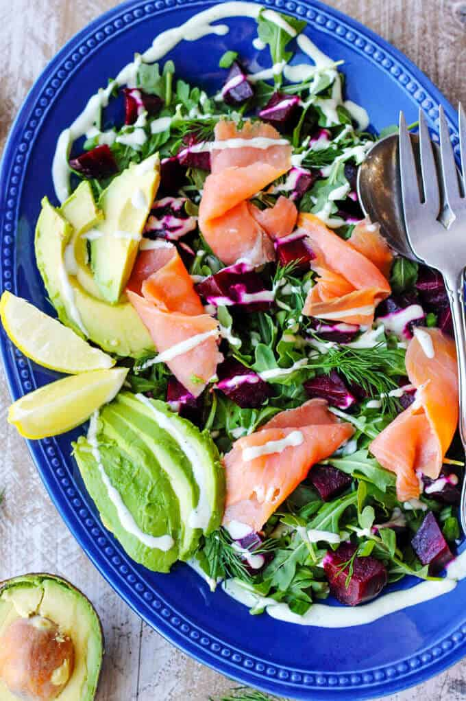 Smoked Salmon and Roasted Beets Salad with avocado, lemon slices a Goat Cheese Dressing on a blue plate with fork and spoon, half avocado on a side