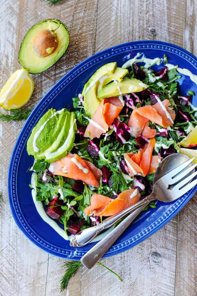Smoked Salmon and Roasted Beets Salad with avocado, lemon quarters and a Goat Cheese Dressing on a blue pate placed diagonal with fork and spoon; with half avocado and lemon on a side