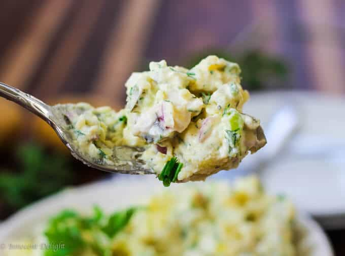 Potato Salad with eggs and pickles on a fork