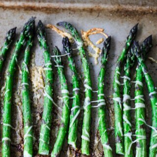 Roasted asparagus with Parmesan Cheese on a sheet pan, vertical photo