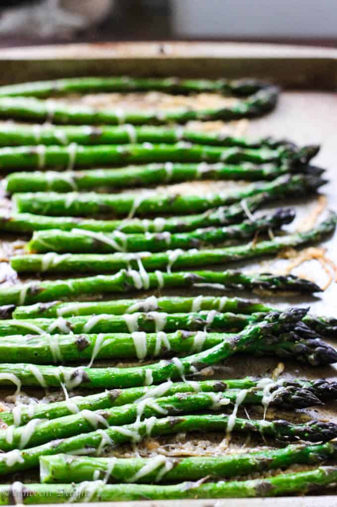 Roasted asparagus with parmesan cheese on a sheet pan side ways view