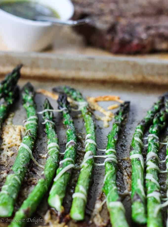 Roasted asparagus with parmesan cheese on a sheet pan straight shot