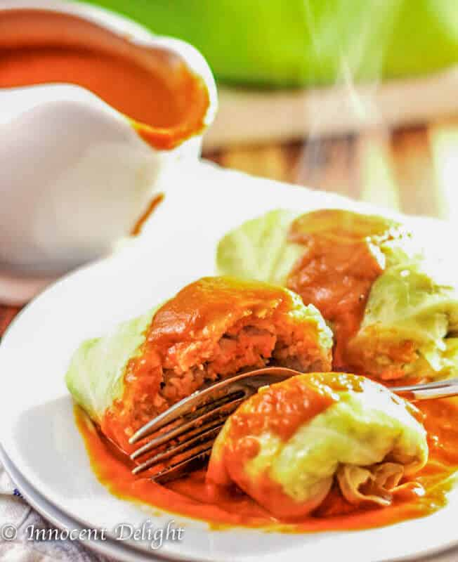Polish Stuffed Cabbage Rolls On white plate with tomato sauce and fork