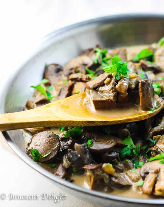 Creamy Mushroom Sauce in skillet with wooden spoon.