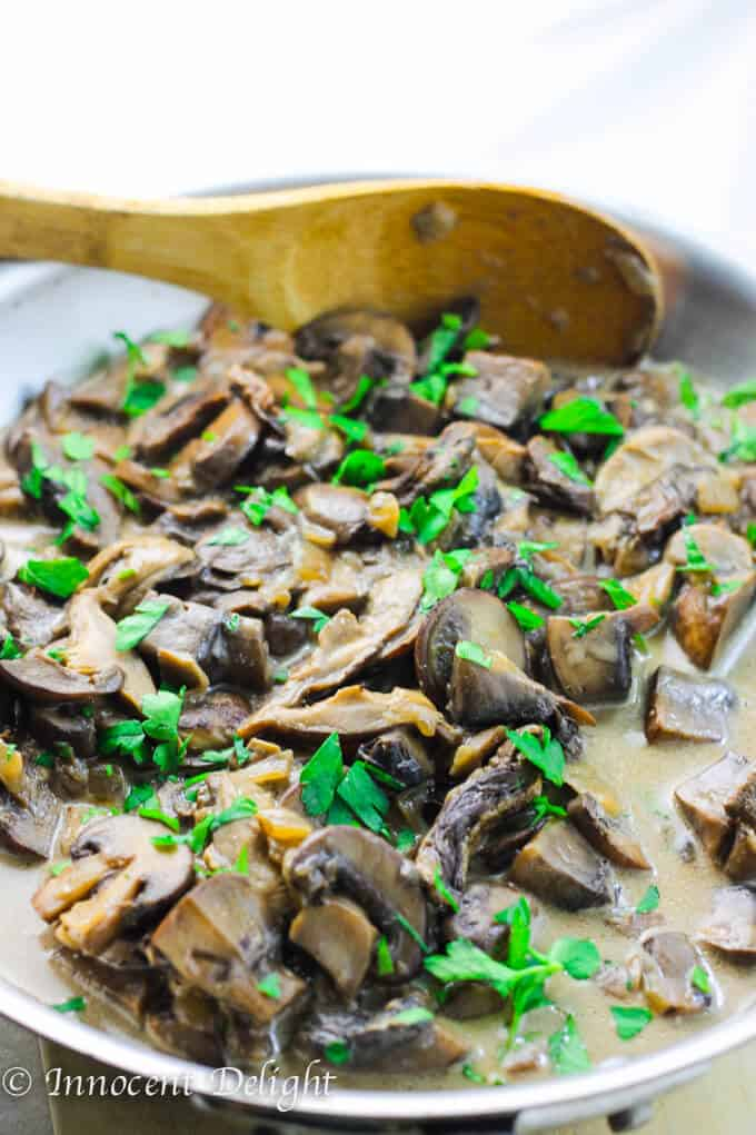 Creamy Mushroom Sauce with wild and fresh mushrooms in a skillet with spoon.