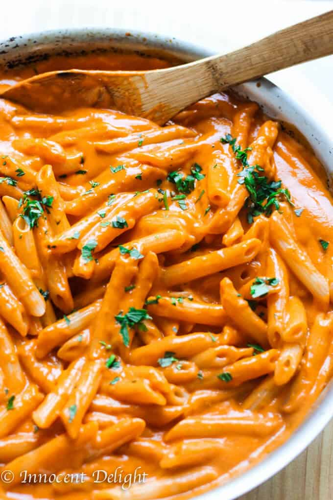 Pasta in vodka sauce in a skillet with wooden spoon