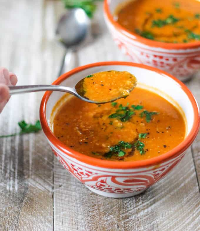 Tomatoes Red Lentils Coconut Soup on a spoon and in orgnge bowls
