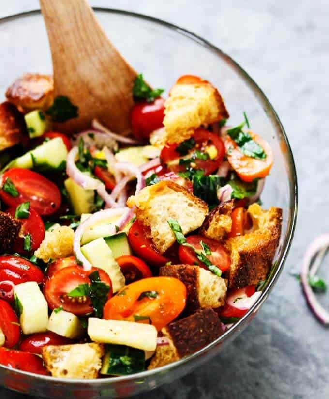 Italian Bread Salad with tomatoes, onions and cucumbers in a bowl with wooden spoon.