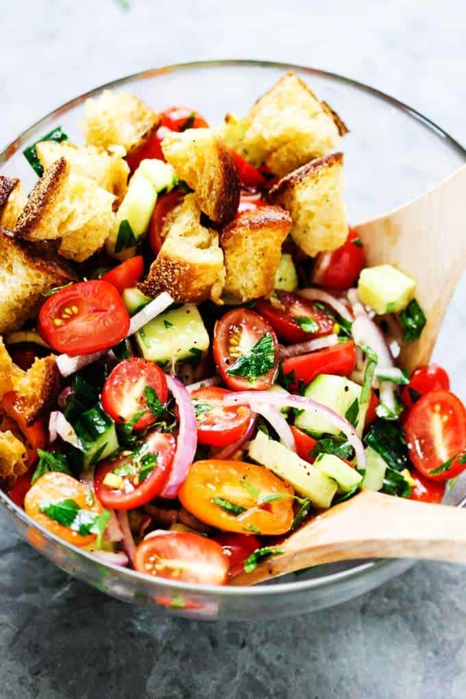 Panzanella Salad in a glass bowl with two wooden spoons.