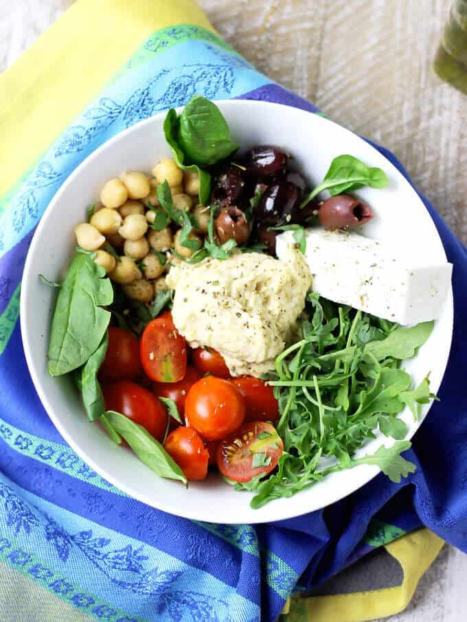Mediterranean Hummus Bowl with tomatoes, feta and olives in a white bowl on top of colorful kitchen towel