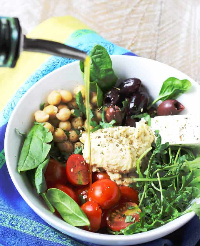 Mediterranean Hummus Bowl with feta tomatoes greens olives and chickpeas with olive oil pouring over the bowl
