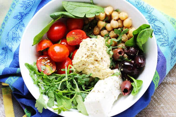 Mediterranean Hummus Bowl -on a kitchen towel with tomatoes, spinach, chickpeas and feta