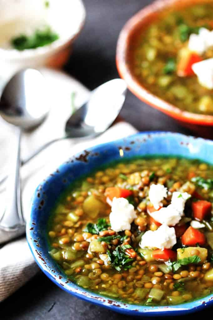 Bowls of Greek lentils soup with feta with spoons on a side
