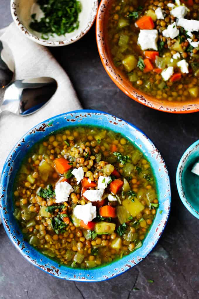 Two bowls: blue and orange of Fakes (Greek Lentil Soup) with feta with spoon and chopped parsley on a side.