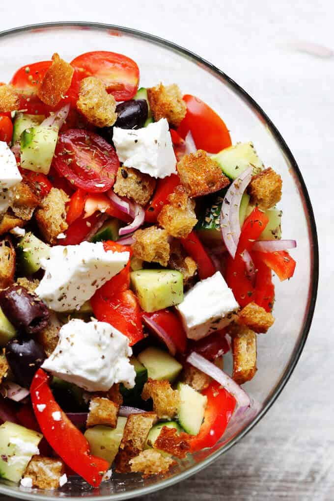 Greek Panzanella Salad with tomatoes, peppers, cucumbers, olives, feta and bread cubes in a glass bowl
