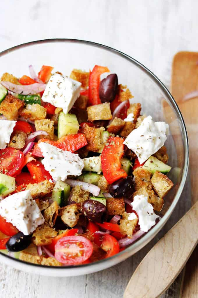 Greek salad with bread cubes in a bowl;