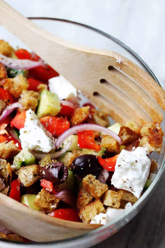 Greek Panzanella Salad in a bowl with wooden spoon and fork, combines traditional Greek salad flavors, like Kalamata olives, and tangy feta with bread cubes toasted in tasty garlicky vinaigrette.