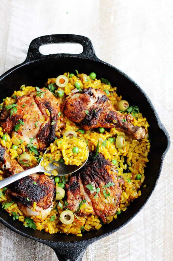 Chicken saffron rice with olives and peas in a skillet with the spoon