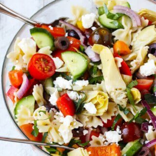 Farfalle Pasta Salad Mediterranean Style is a great pasta salad with super fresh ingredients like cucumbers, tomatoes, onions and peppers. Extra flavors come form Kalamata Olives, marinated artichokes and feta cheese. Dressed with red wine based vinaigrette instead of mayo makes for super light and refreshing side dish.