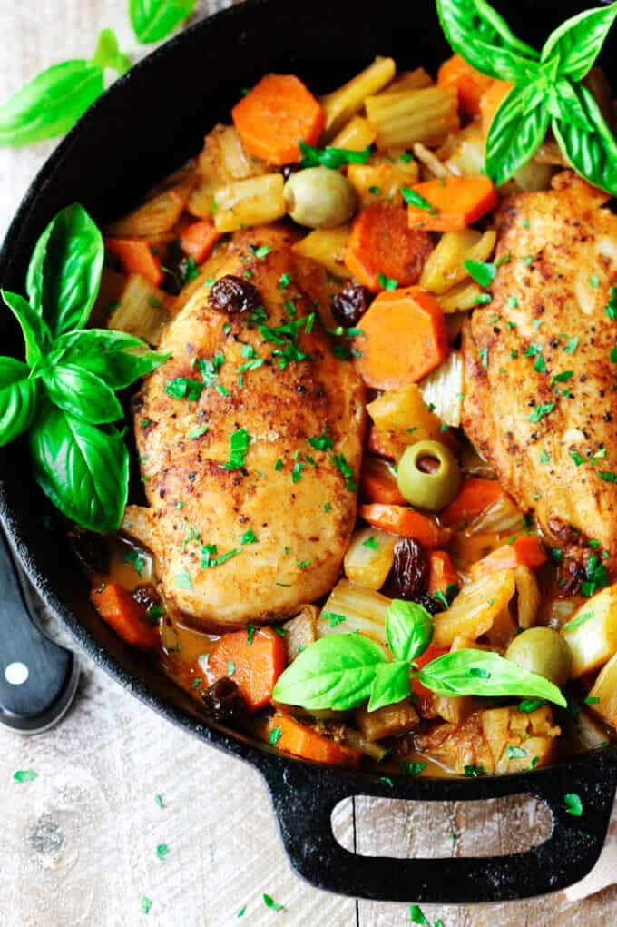 Fennel Chicken Mediterranean Style with carrots, raisins and olives in a skillet