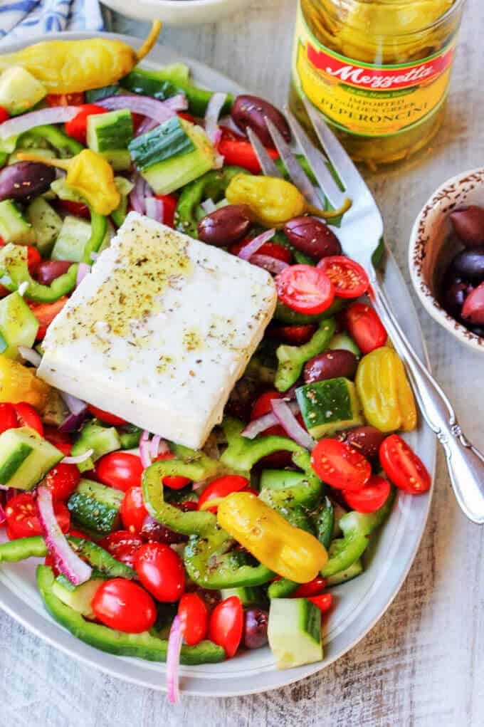 Horiatiki Greek Salad on a plate with big feta slice on top and jar of peperoncini on a side