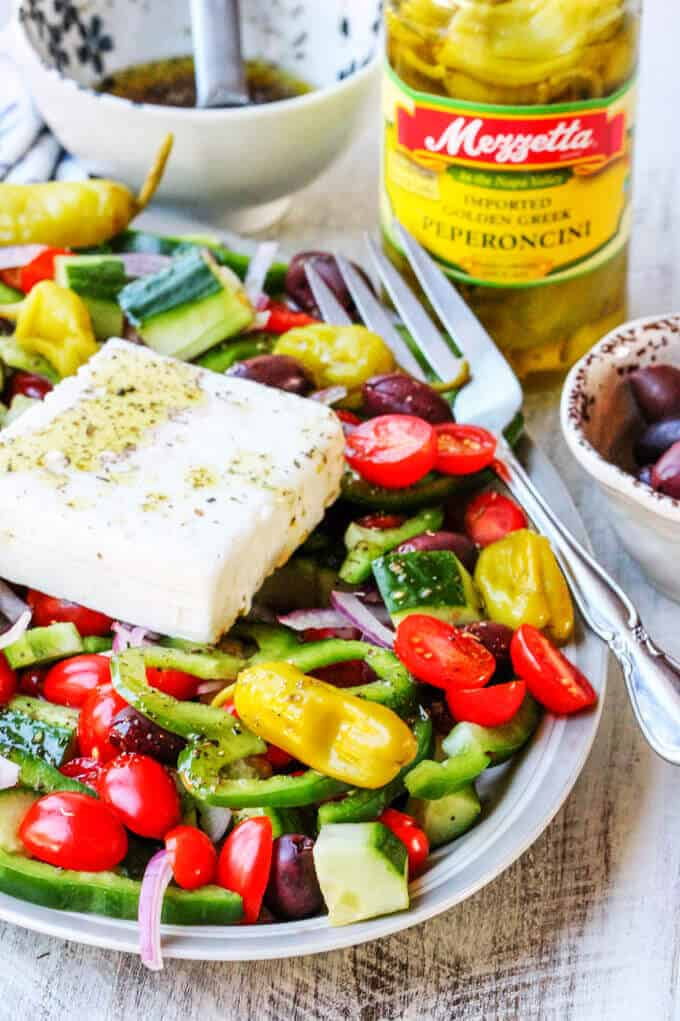 Greek salad on a plate with Mozzetta peperoncini jar in the back