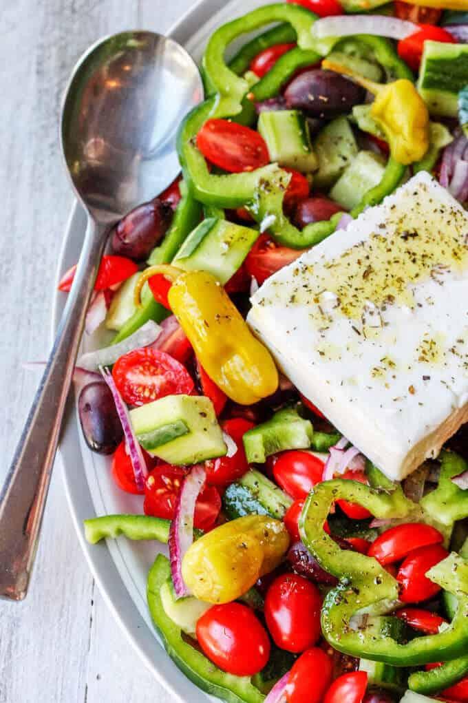 Greek Salad on a plate with spoon on a side