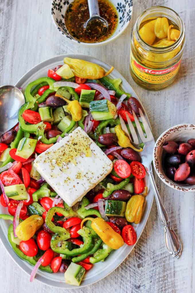 Greek village salad on a plate, with olives, dressing and jar of peppers on a side