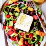 Horiatiki Greek Salad on a plate with jar of peppers on a side