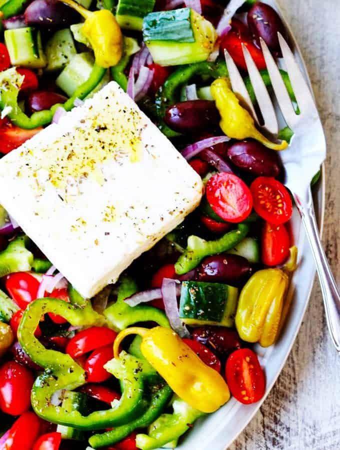 Horiatiki or Greek Salad on a plate with feta and fork