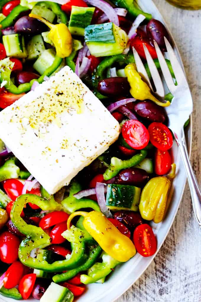 Horiatiki Salad or Greek Salad on a plate with feta and fork