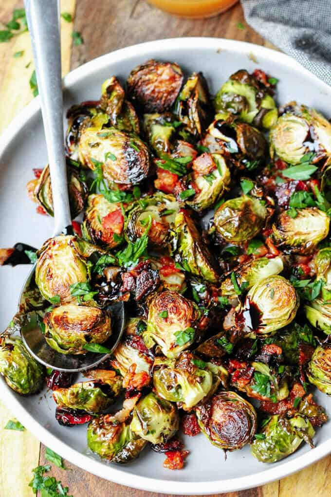 Balsamic Glazed Brussels Sprouts with Bacon, cranberries on a plate with spoon.