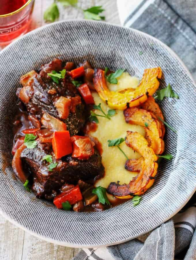 Red Wine Braised Short Ribs with Parmesan Polenta and Roasted Delicata Squash, is a super flavorful dinner idea that will make you feel warm and cozy on a cold, winter night.
