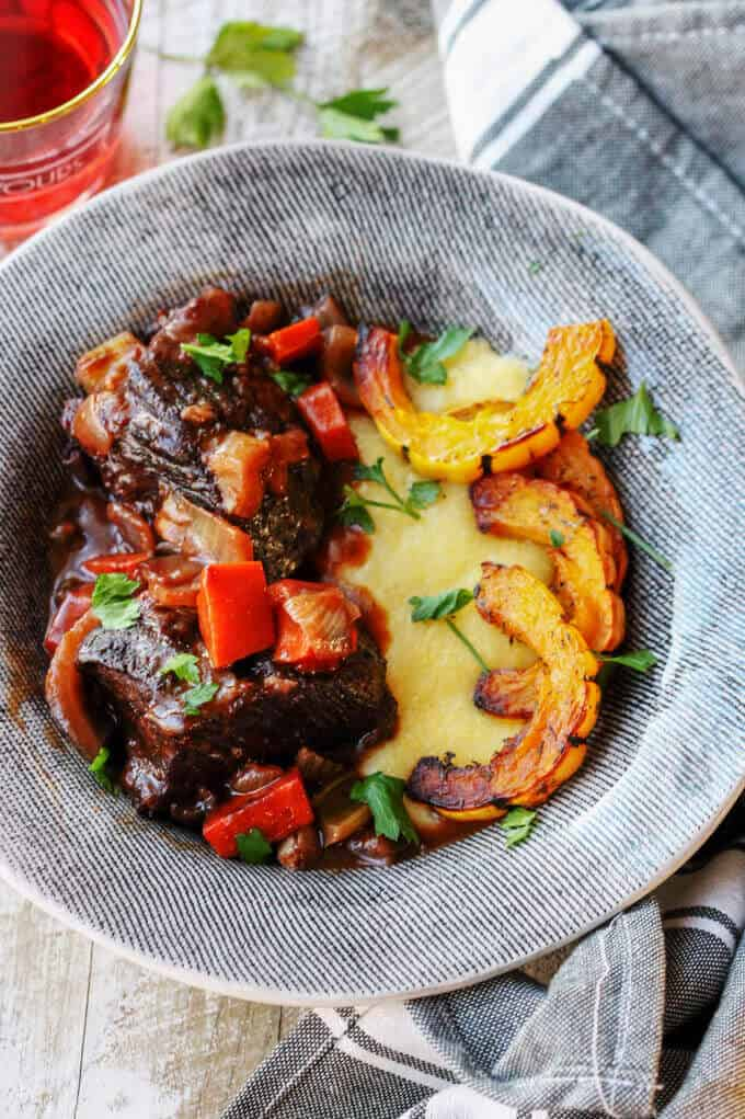 Red Wine Braised Short Ribs with Parmesan Polenta and Roasted Delicata Squash in a grey plate with kitchen towel and drink on a side