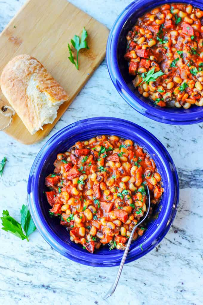 Two blue plates with breton beans, sausage and tomatoes; piece of bread on a cutting board