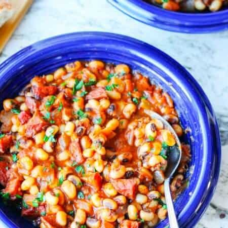 beans with sausage and tomatoes on blue plate with spoon
