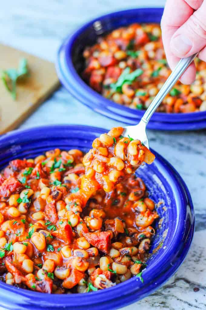 two plates with breton beans, sausage and tomato sauce with hand holding spoon with beans