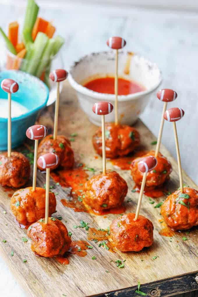 Buffalo Turkey Meatballs with football sticks and hot sauce and blue cheese on a side