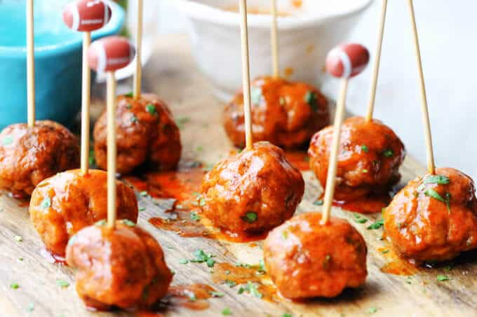 Buffalo Turkey Meatballs with football sticks and bowls with sauces in the back, vertical