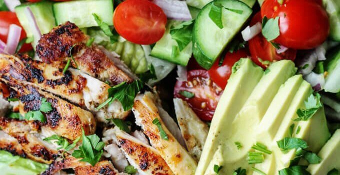 Garlic Lemon Chicken Salad with lettuce, tomato, cucumber, onions, avocado on a plate, dressing in the bowl