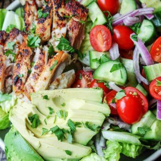 Garlic Lemon Chicen Salad with lettuce, tomatoes, cucumber, onions, avocado; vertical
