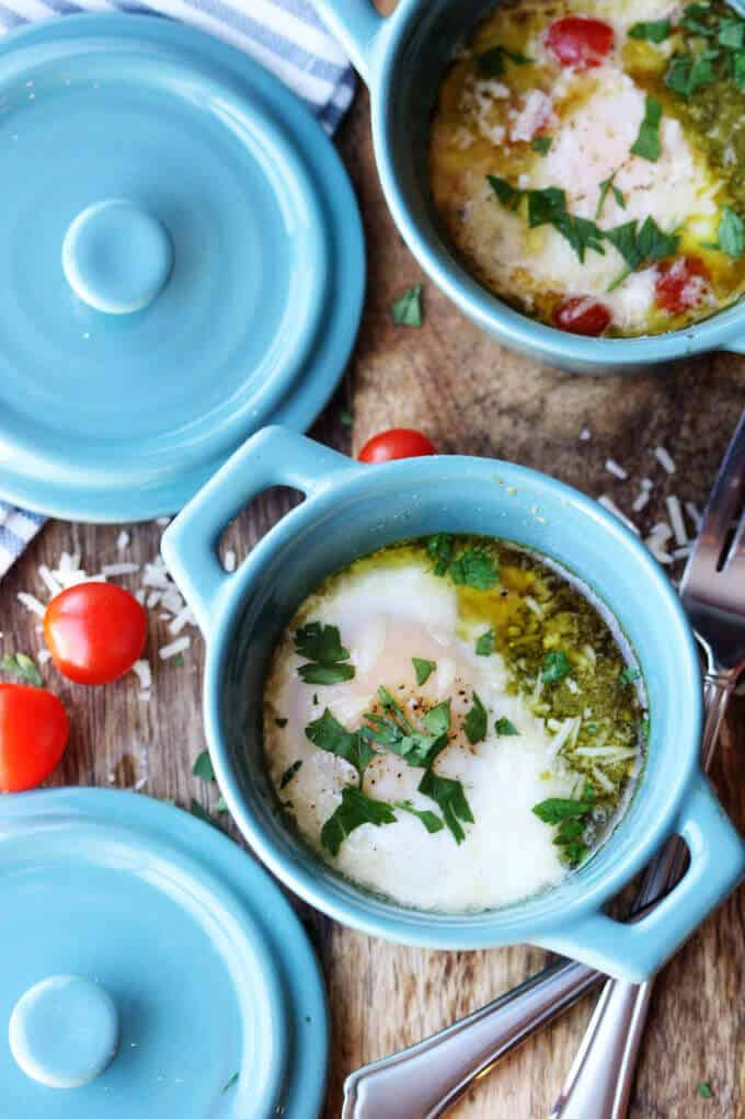 two ramekins with baked eggs with tomatoes and pesto