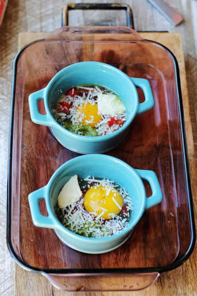 ramekins with cracked eggs in baking dish