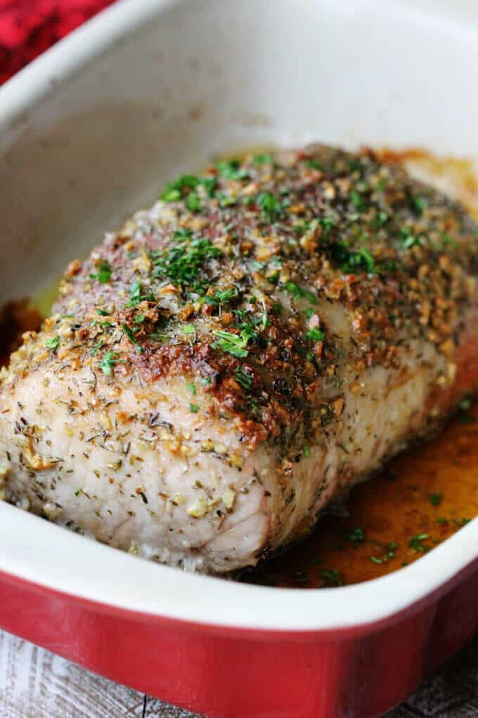 Brown sugar pork loin with garlic and herbs in red baking dish, close up
