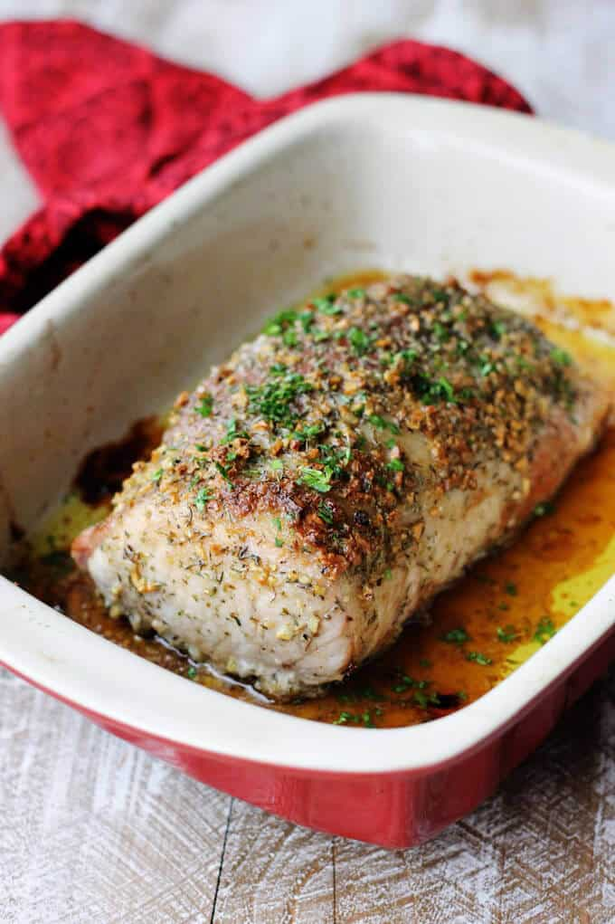 Brown sugar pork loin in the baking dish with red napkin in the back