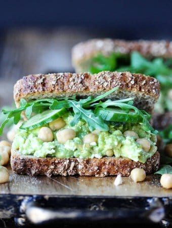 Smashed Chickpea Avocado Feta Sandwich with cucumber and arugula, front close up