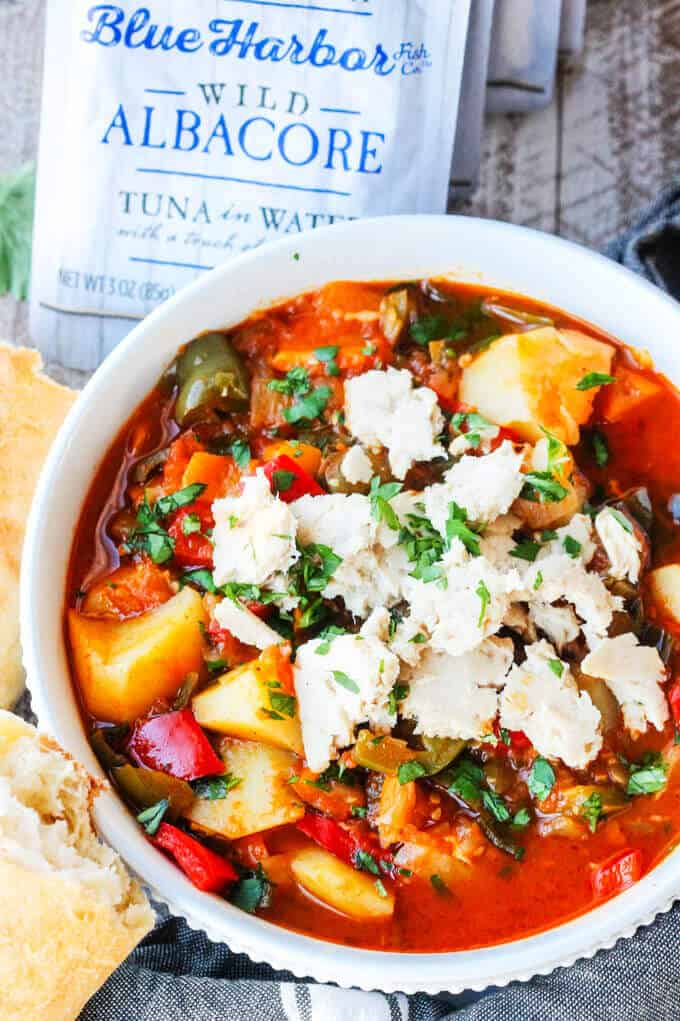 Spanish style tuna stew in a white bowl with bread on a side with tuna pouch at the back