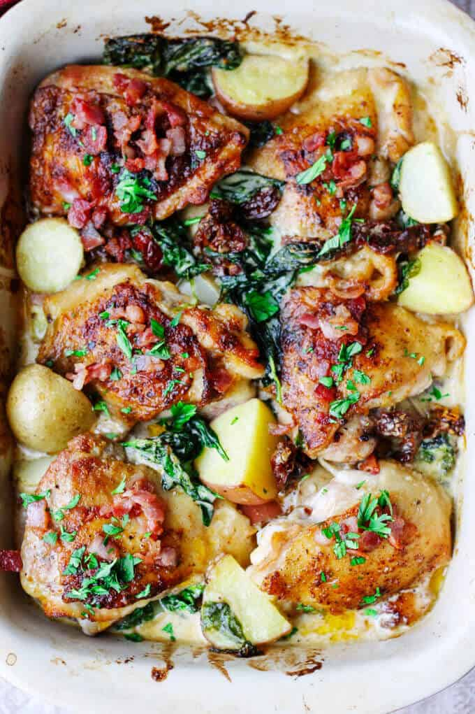 Tuscan chicken and potatoes in baking dish, overhead view