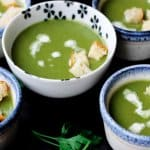Creamy spinach soup with croutons on bowls